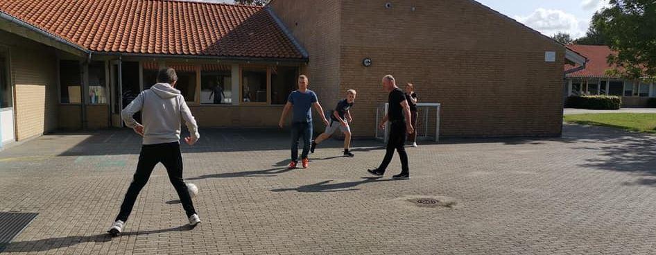 Elever spiller fodbold i skolegården